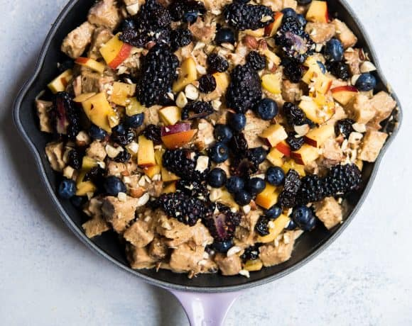 Overhead of blueberry nectarine bread pudding in a light purple cast iron skillet