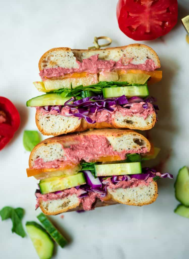 Overhead of rainbow veggie bagel sandwich with beet hummus sliced in half on a white tray