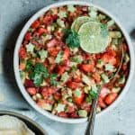 Bowl of strawberry avocado salsa in a white bowl garnished with lime