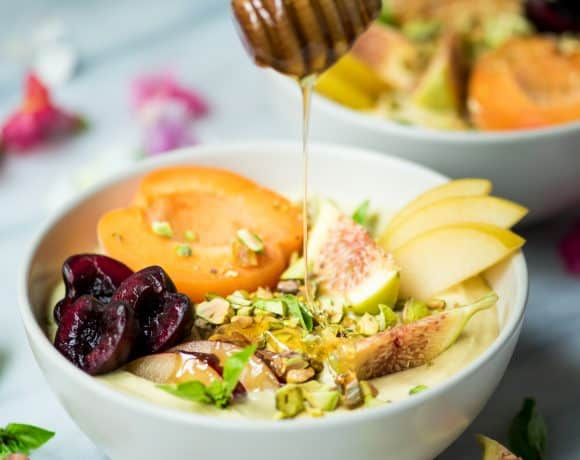 Drizzling honey onto yogurt bowl topped with fresh fruit and pistachios