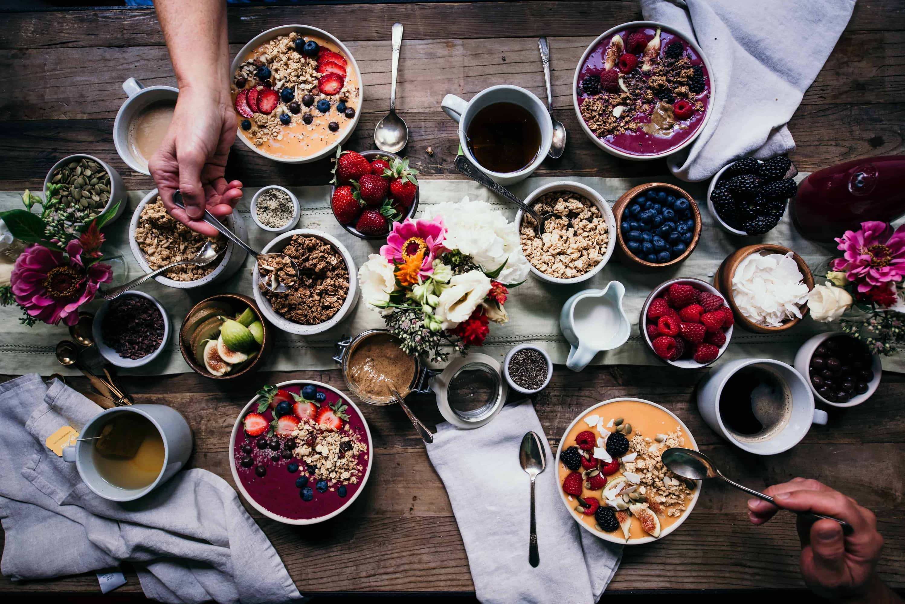 Overhead of breakfast tablescape with smoothie bowls, bowls of fresh fruit, granola, flowers, tea, coffee