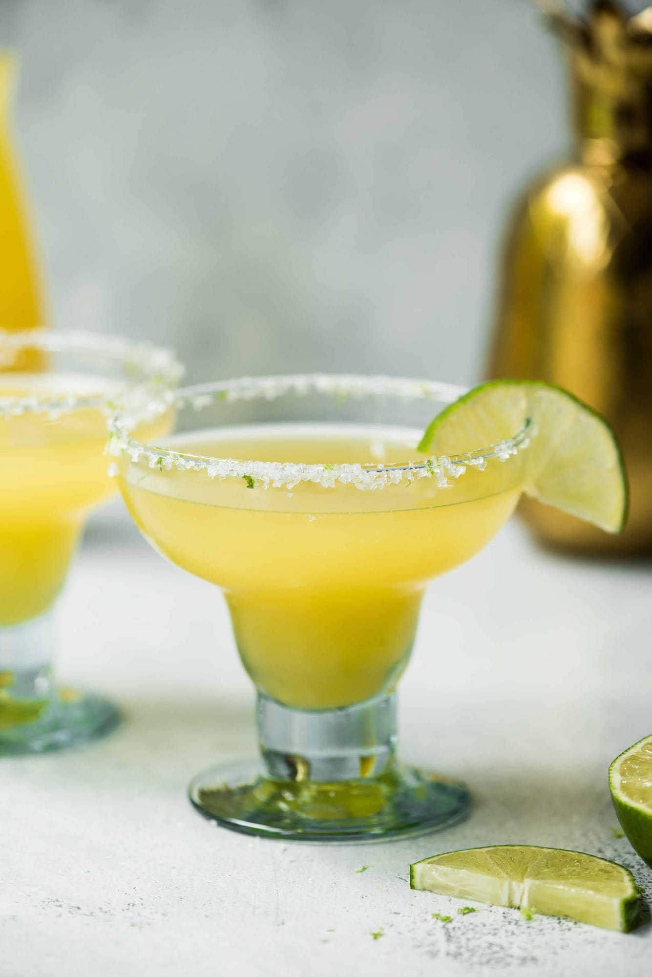 Pineapple jalapeno margarita garnished with lime on a white background