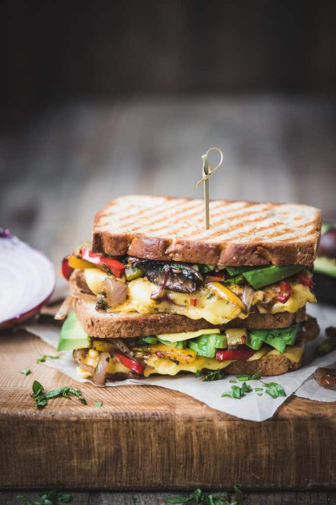 Side view of two stacked fajita paninis with veggies and vegan cheese on a rustic wood cutting board
