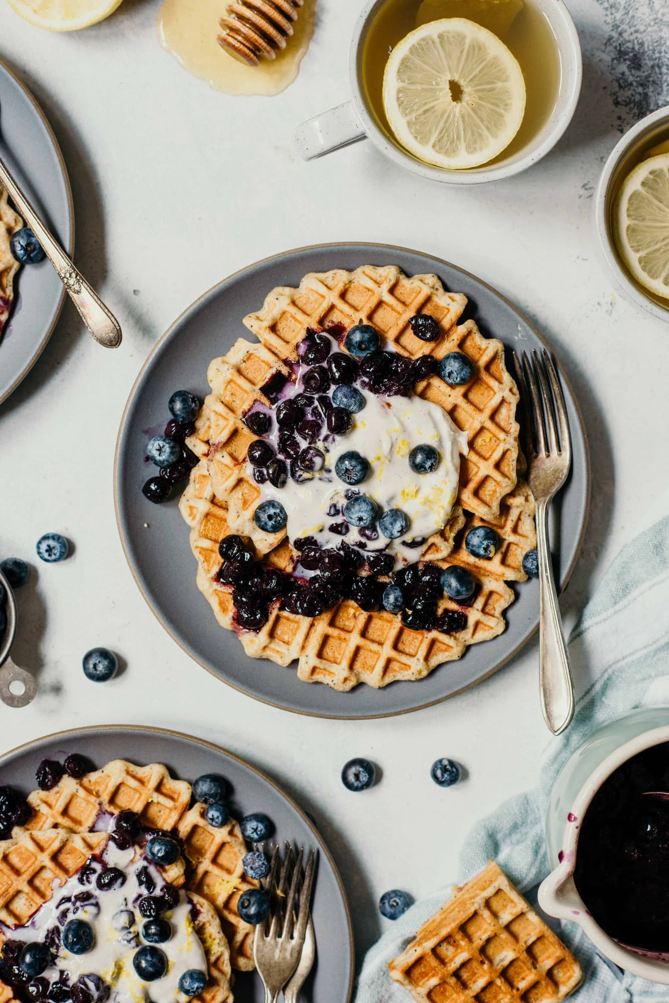 Overhead of lemon blueberry poppyseed waffles topped with whipped cream and blueberries on a white background