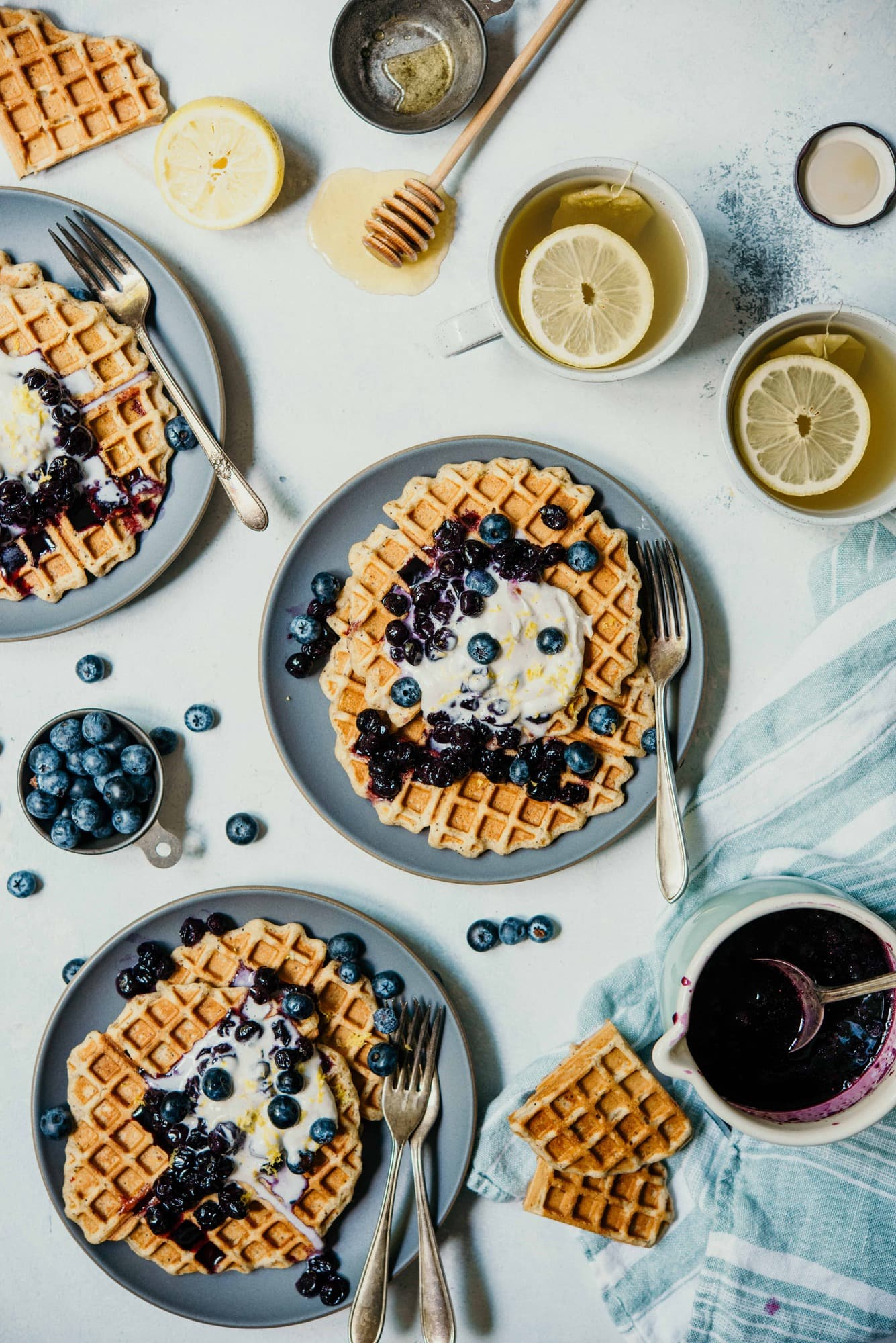 Overhead of 3 plates of lemon blueberry poppyseed waffles topped with whipped cream and blueberries on a white background