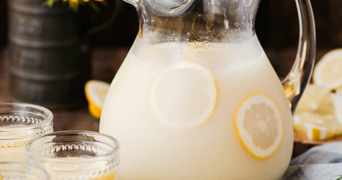 Side view of homemade lemonade in a large vintage pitcher on a wood surface with sunflowers in the background
