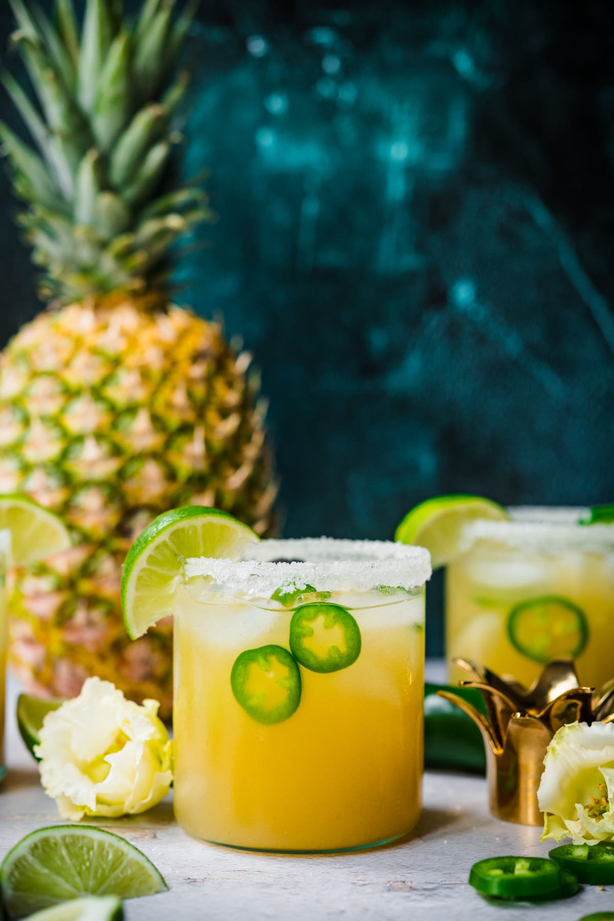 side view of pineapple jalapeño margarita in glass rimmed with salt with a fresh pineapple in background.