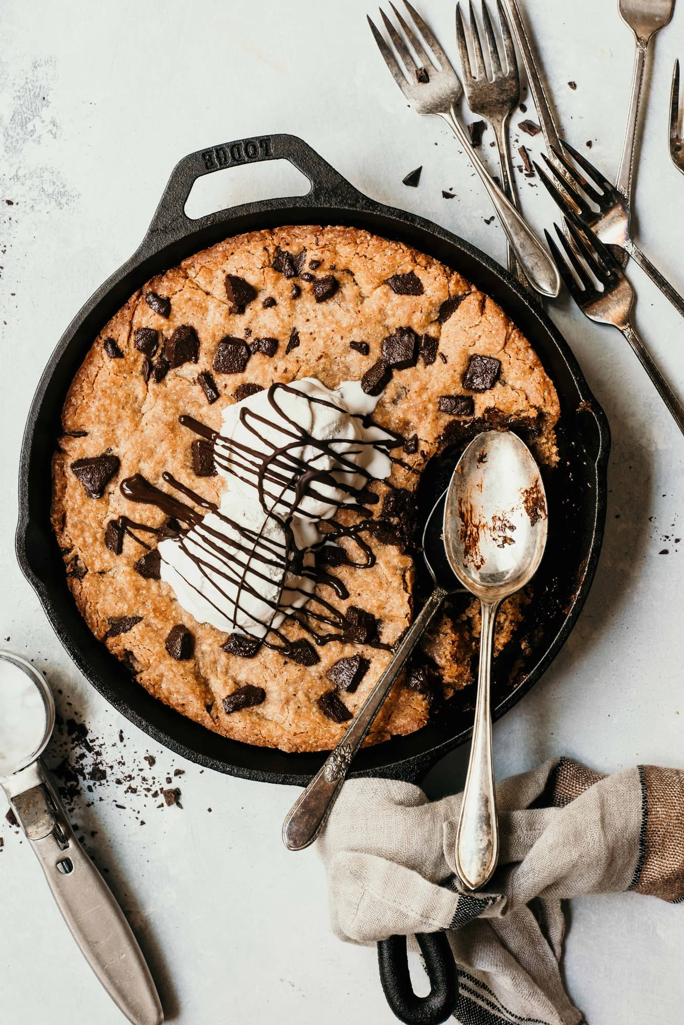 Overhead of a giant chocolate chunk skillet cookie topped with vanilla ice cream and chocolate sauce. Styled on a white background