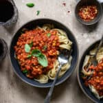 Overhead of zucchini noodles with a vegan bolognese sauce and fresh tomatoes in a large gray bowl on a wood surface