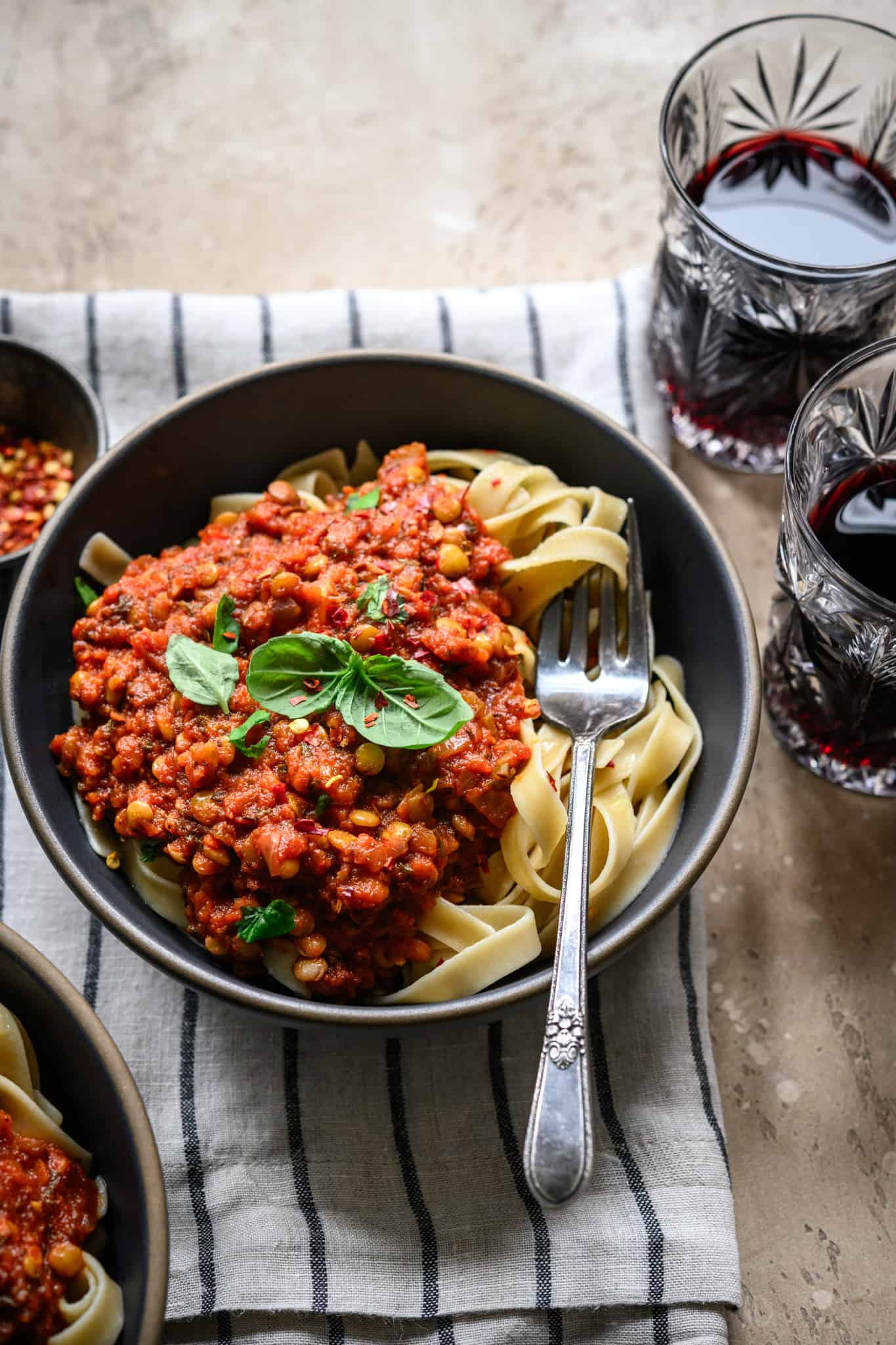 Side view of vegan bolognese served over fettuccine with fresh basil