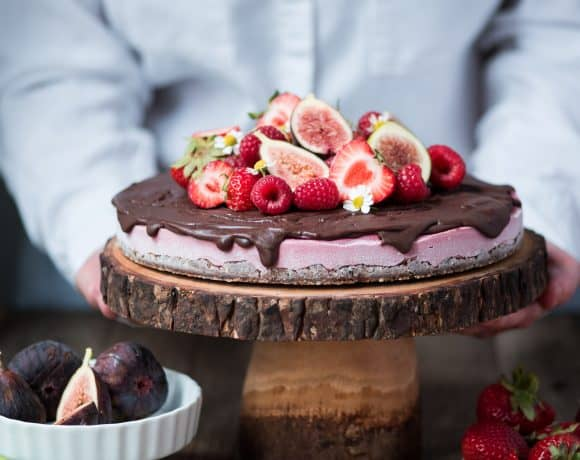 Berry vegan cheesecake with chocolate ganache and fresh fruit on a wood cake stand with person in background picking it up