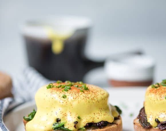 Side view of vegan polenta eggs benedict on a white plate