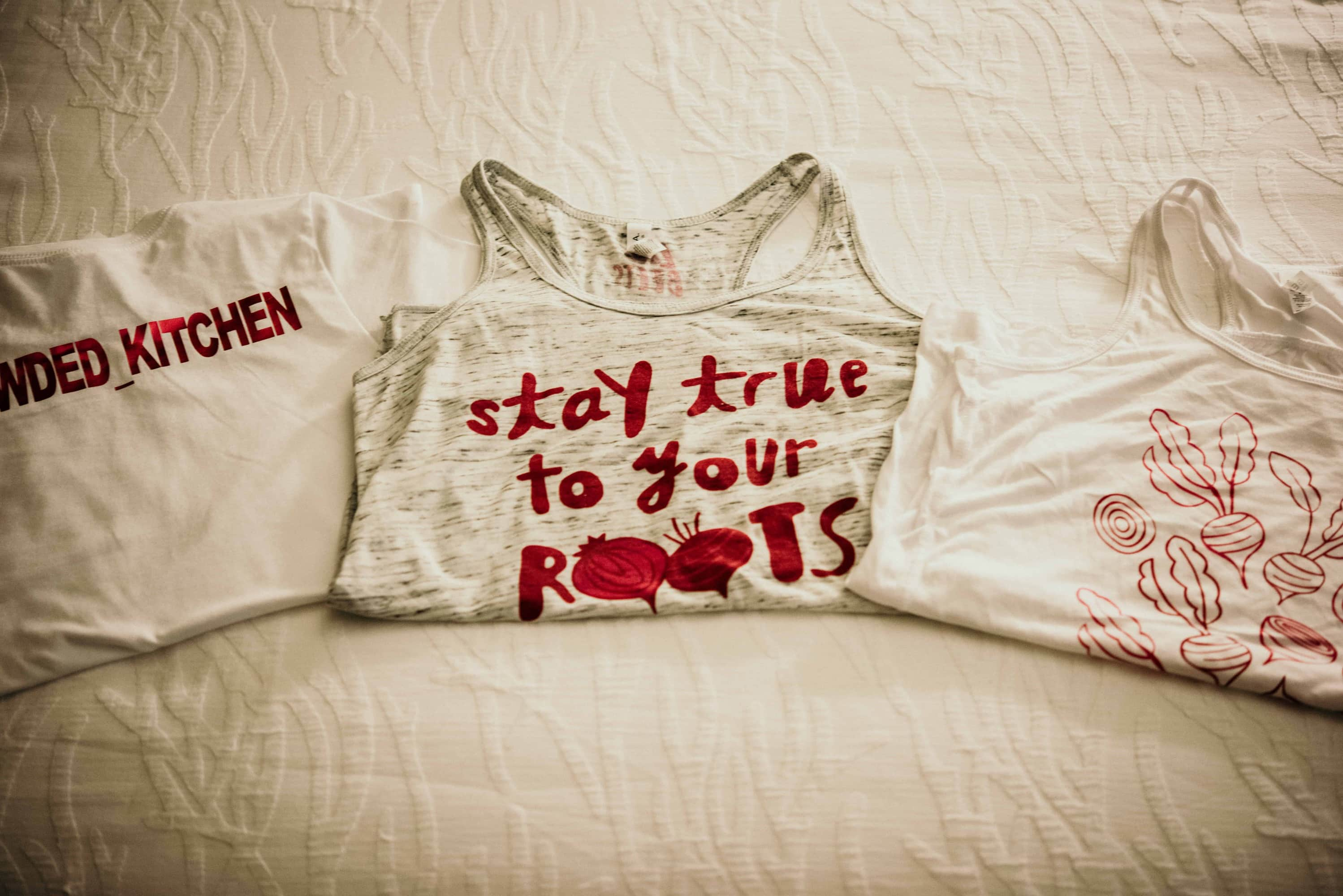 Love beets tank tops folded on a bed with a whit bedspread.