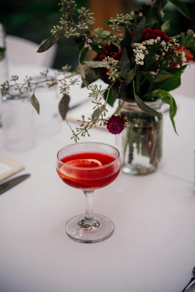 Red drink in a glass on a farm table set for dinner
