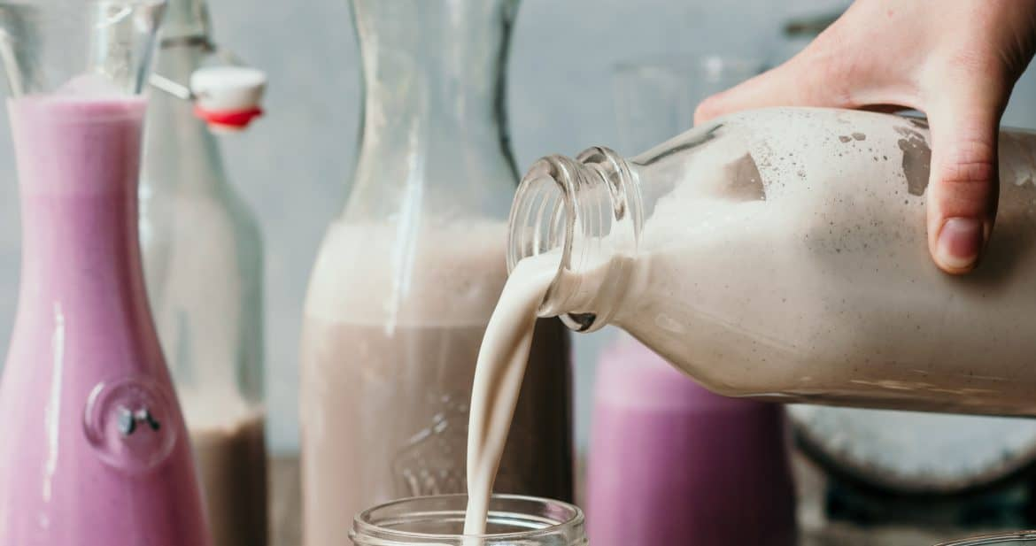 Pouring homemade vanilla almond milk into a glass jar