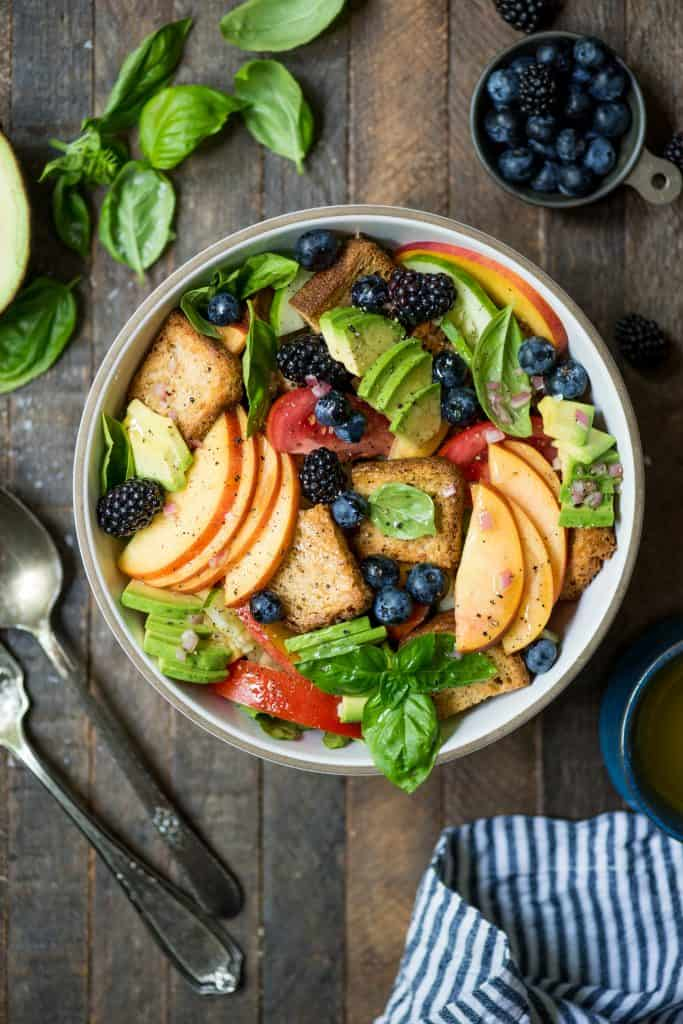 Overhead of Peach Blueberry Panzanella in a white bowl with avocado and fresh basil