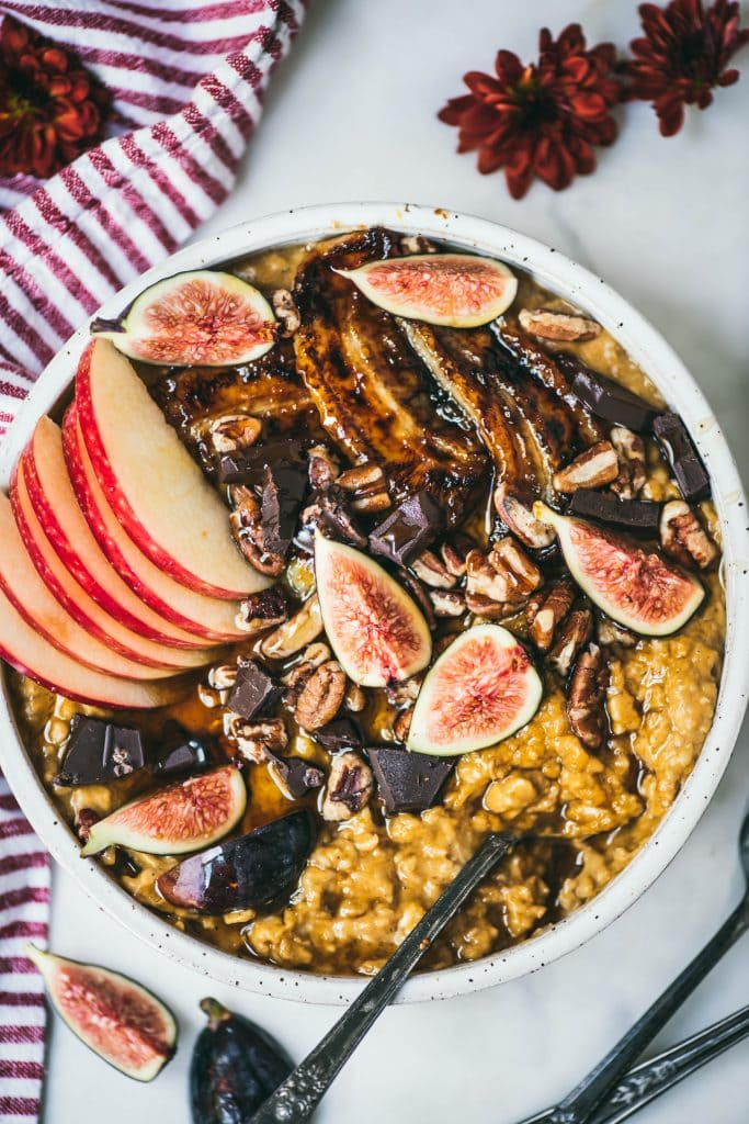 Overhead of a white bowl with pumpkin peanut butter oatmeal topped with caramelized banana, fresh figs, apple, pecans and dark chocolate
