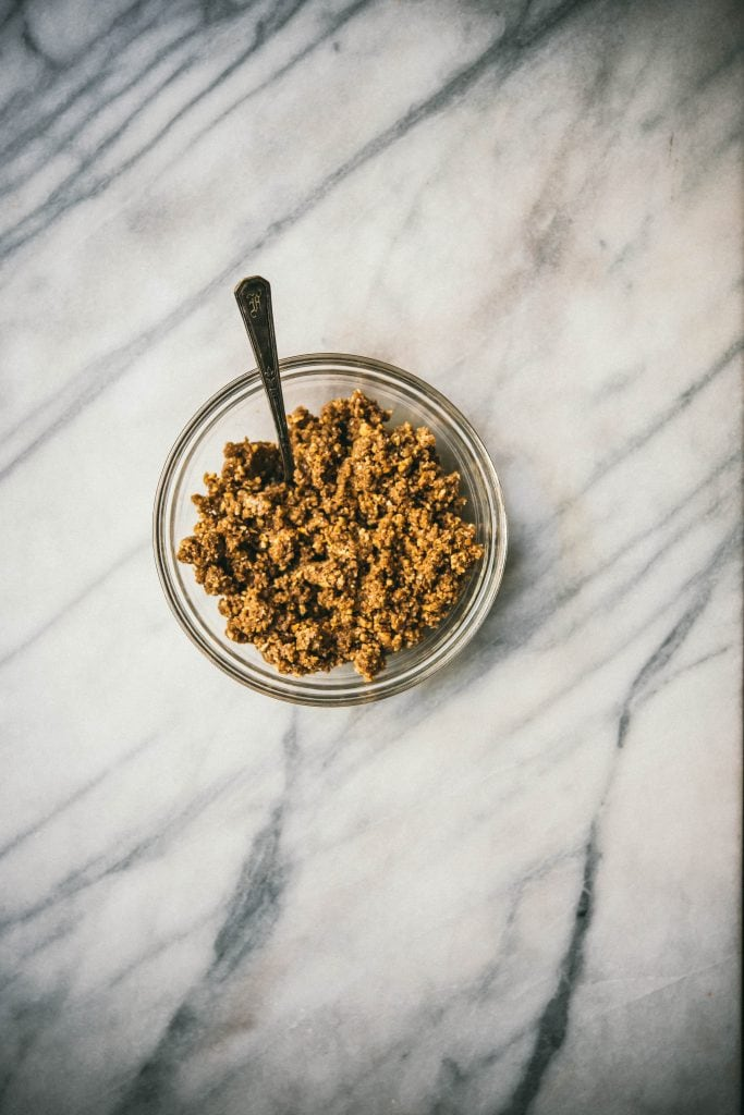 Crunchy chickpea salted caramel tart crust in a bowl on marble surface