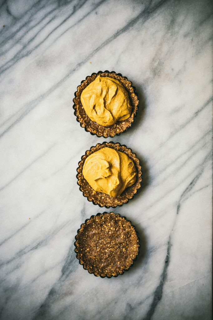 3 mini pumpkin cheesecake tarts on marble surface