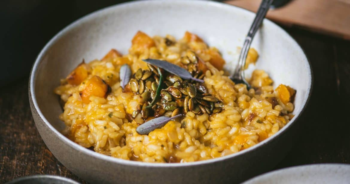 Side view of two bowls of butternut squash risotto with fresh sage. On a rustic wood background