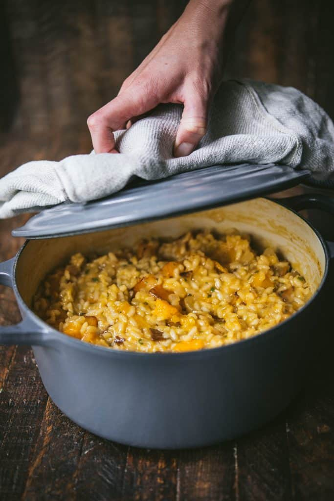 Hand opening pot of butternut squash risotto