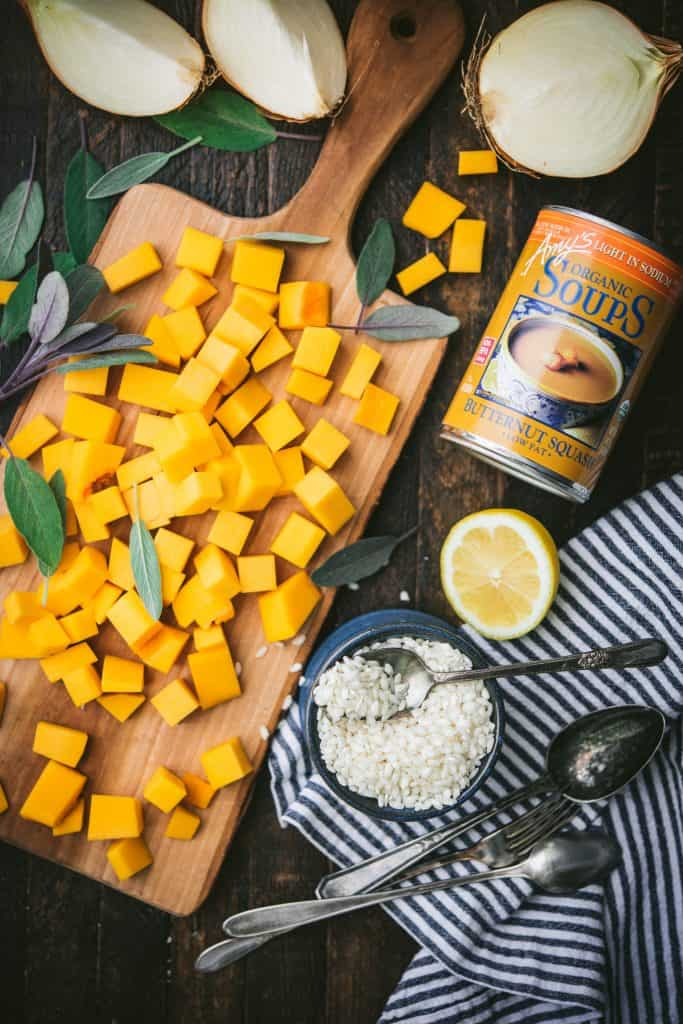 Overhead of wood cutting board with diced butternut squash, next to a bowl of arborio rice, fresh lemon and a can of Amy's butternut squash soup