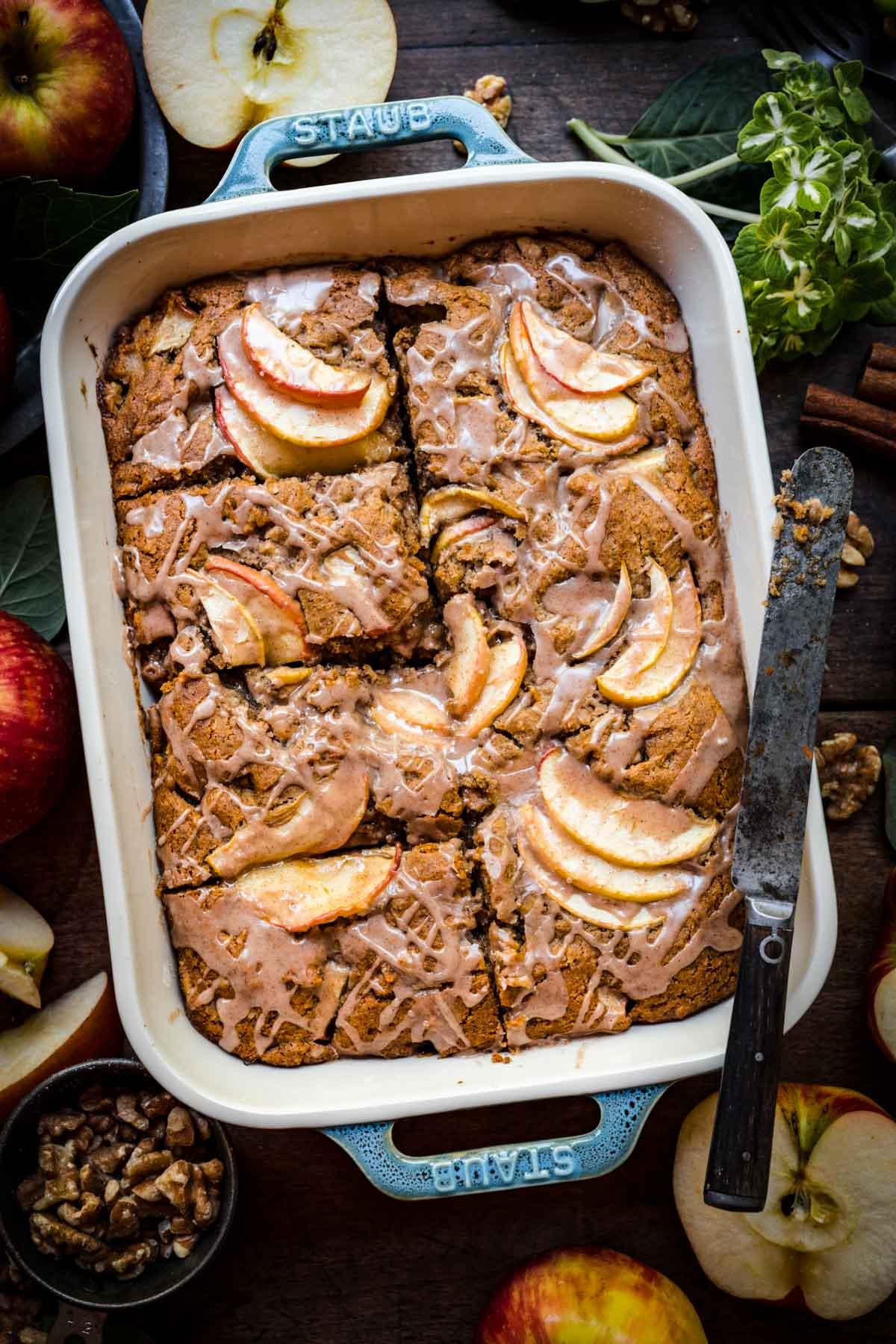 overhead view of vegan apple cake sliced in baking pan with cinnamon glaze.