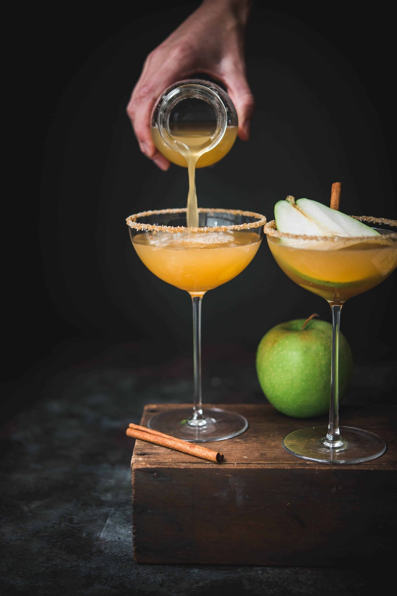 Pouring an apple cider pear martini into long-stemmed coupe glass with dark moody backdrop