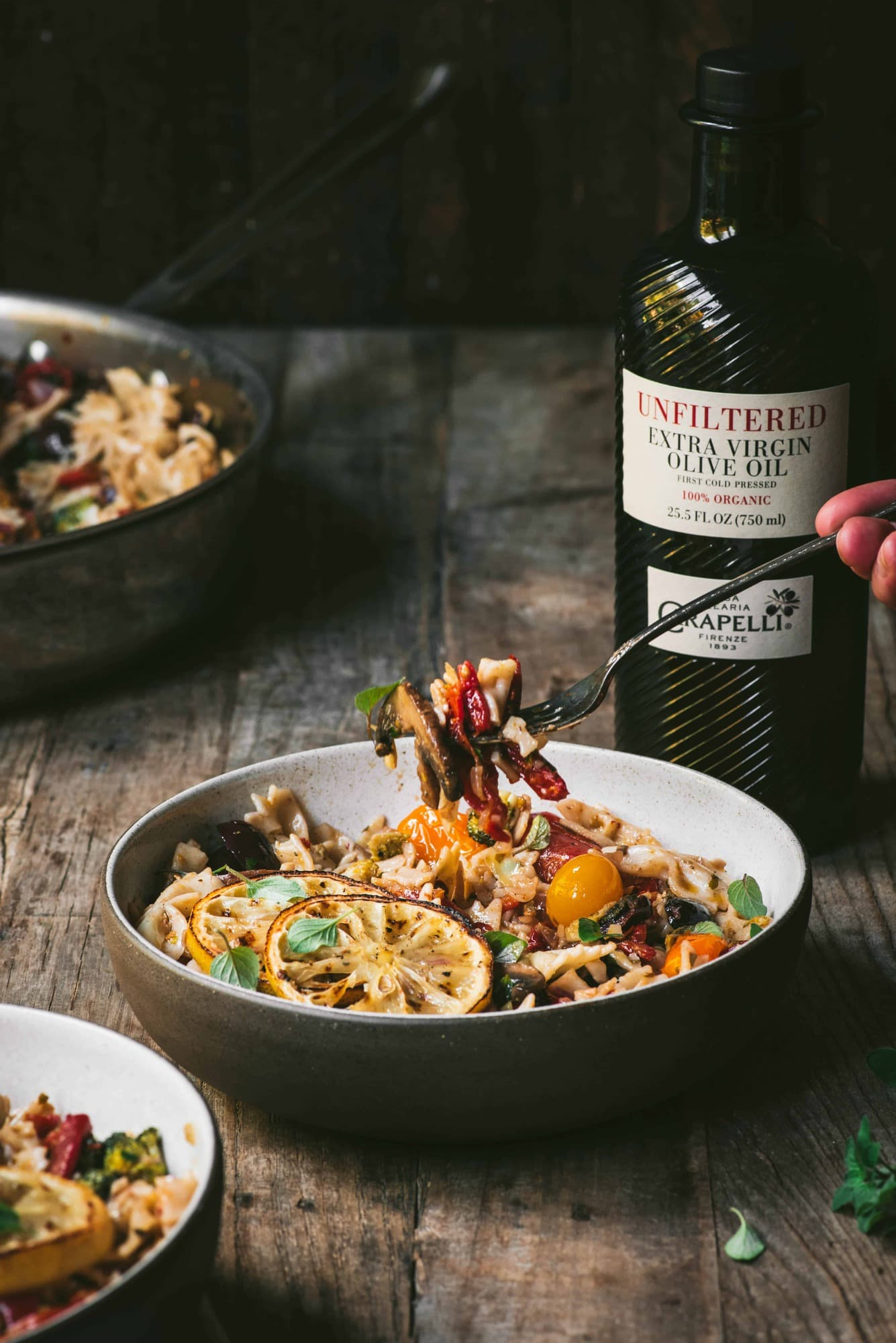 Side view of mediterranean pasta on a fork with bottle of olive oil in background