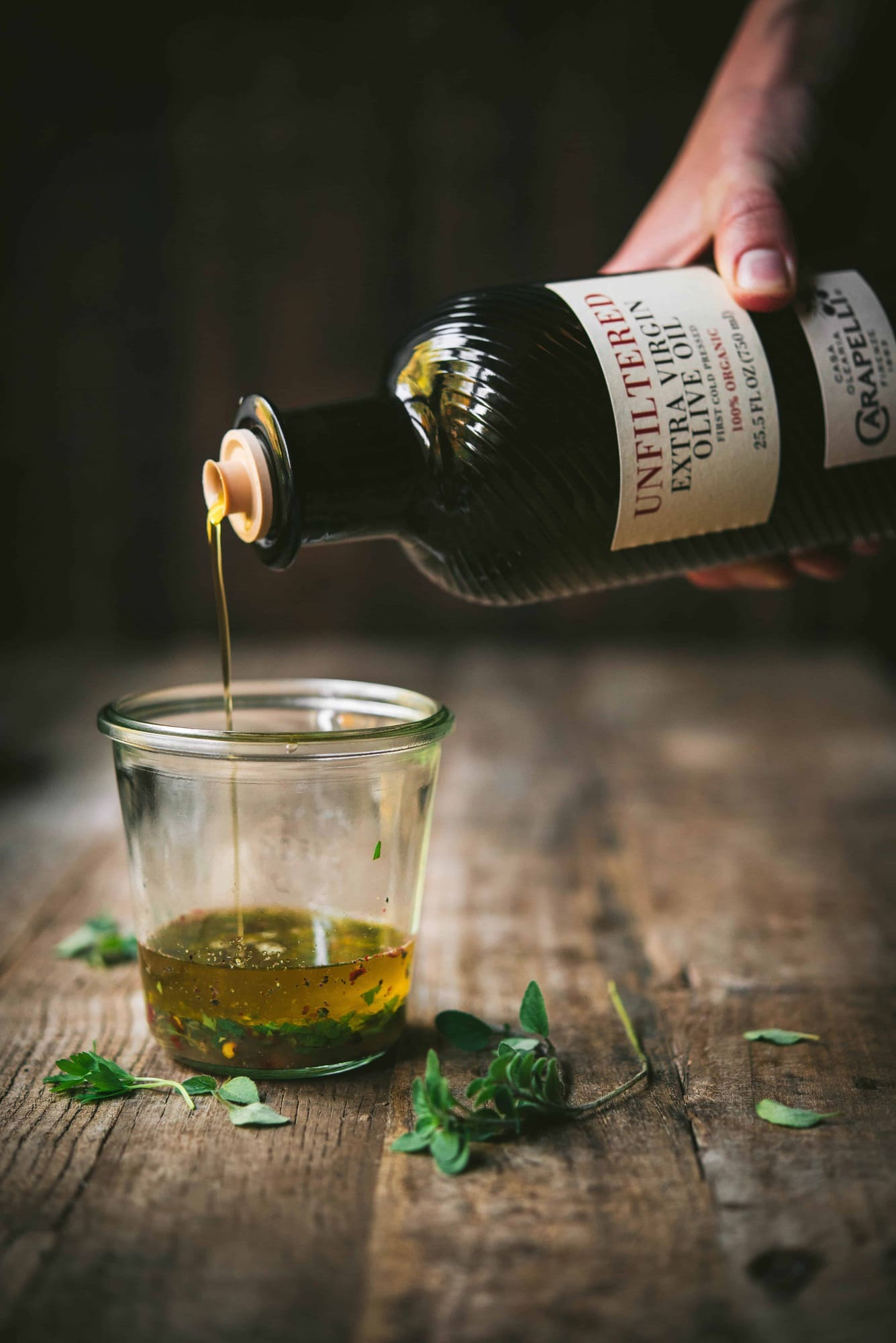 Pouring Carapelli olive oil into glass jar filled with herbs