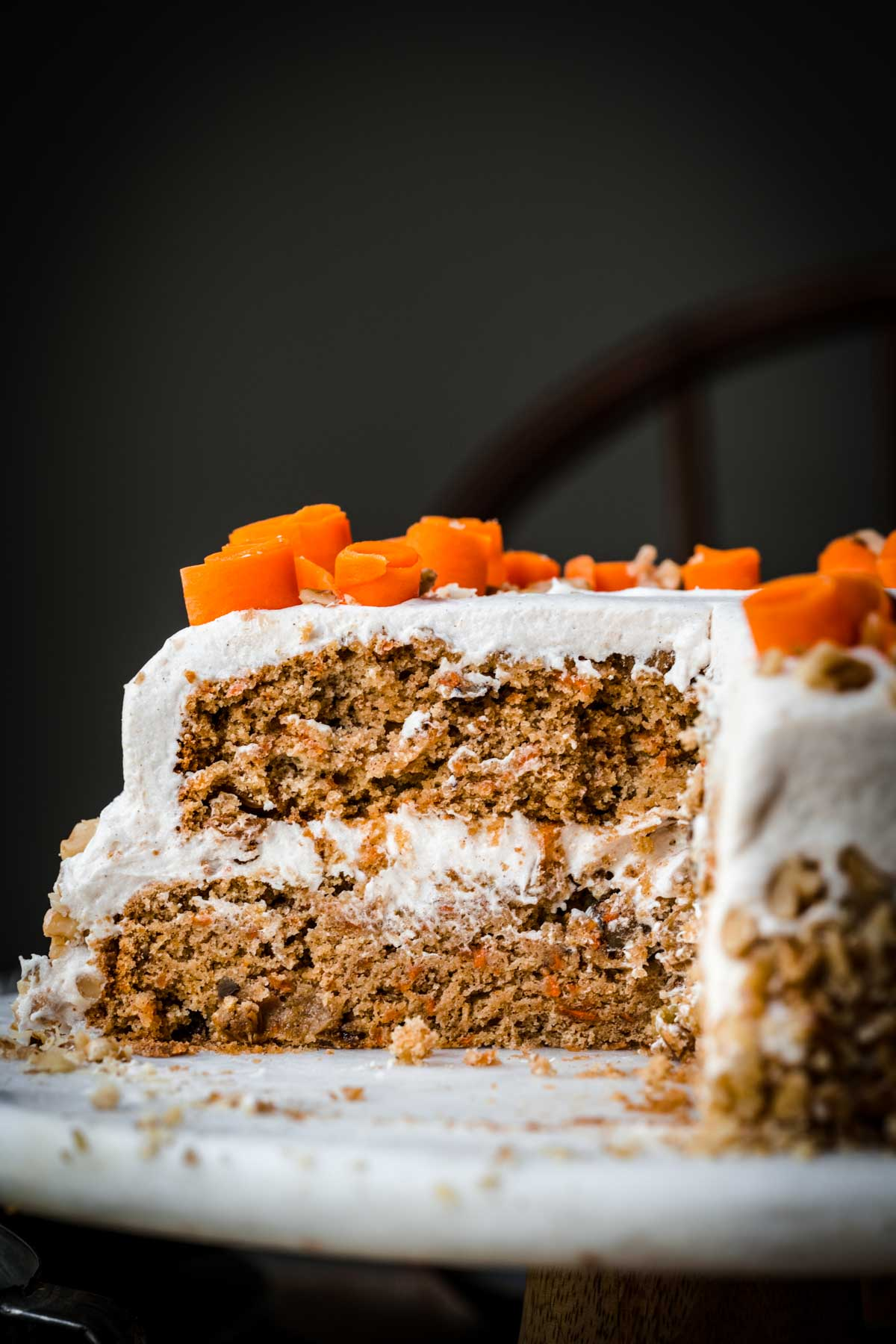 side view of vegan carrot cake slice on cake stand.