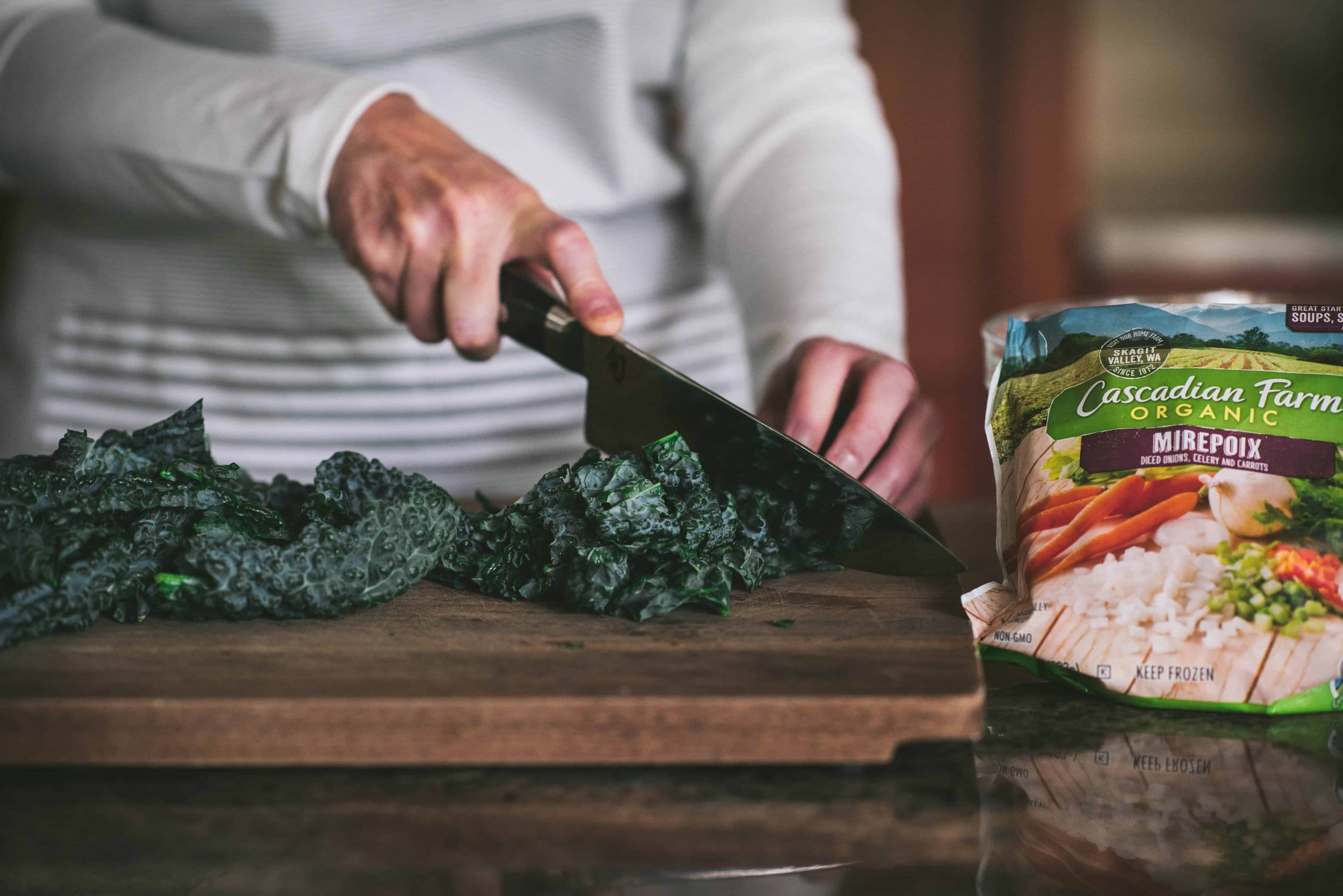 Side view of person slicing kale on cutting board