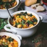45 degree angle of fall vegetable minestrone in a white bowl on a rustic wood background.