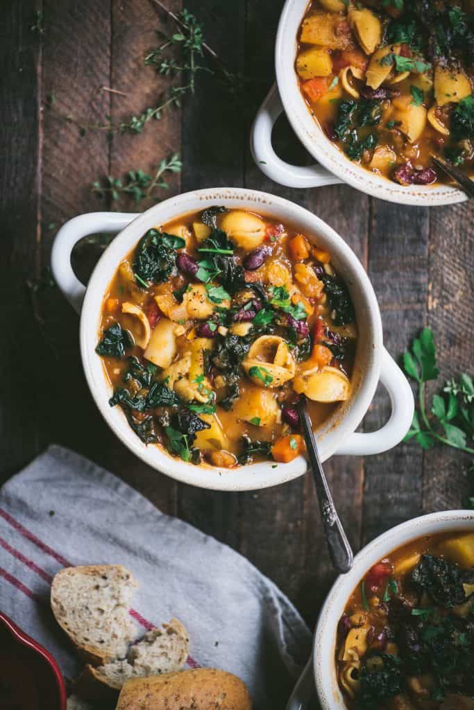 Overhead of fall vegetable vegan minestrone soup in a white bowl