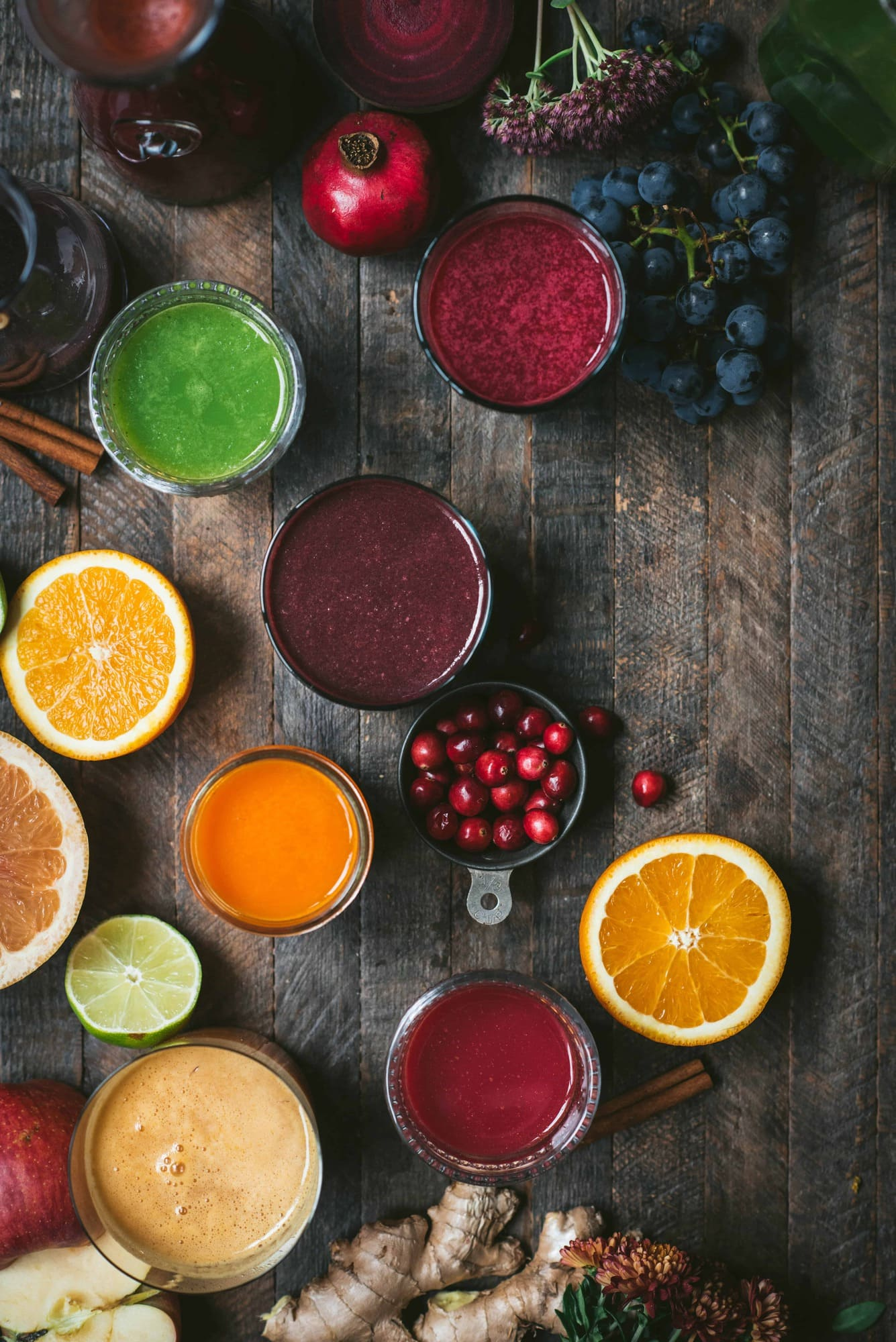 Overhead of colorful fresh glasses of juice and fresh fruit on a rustic wood background