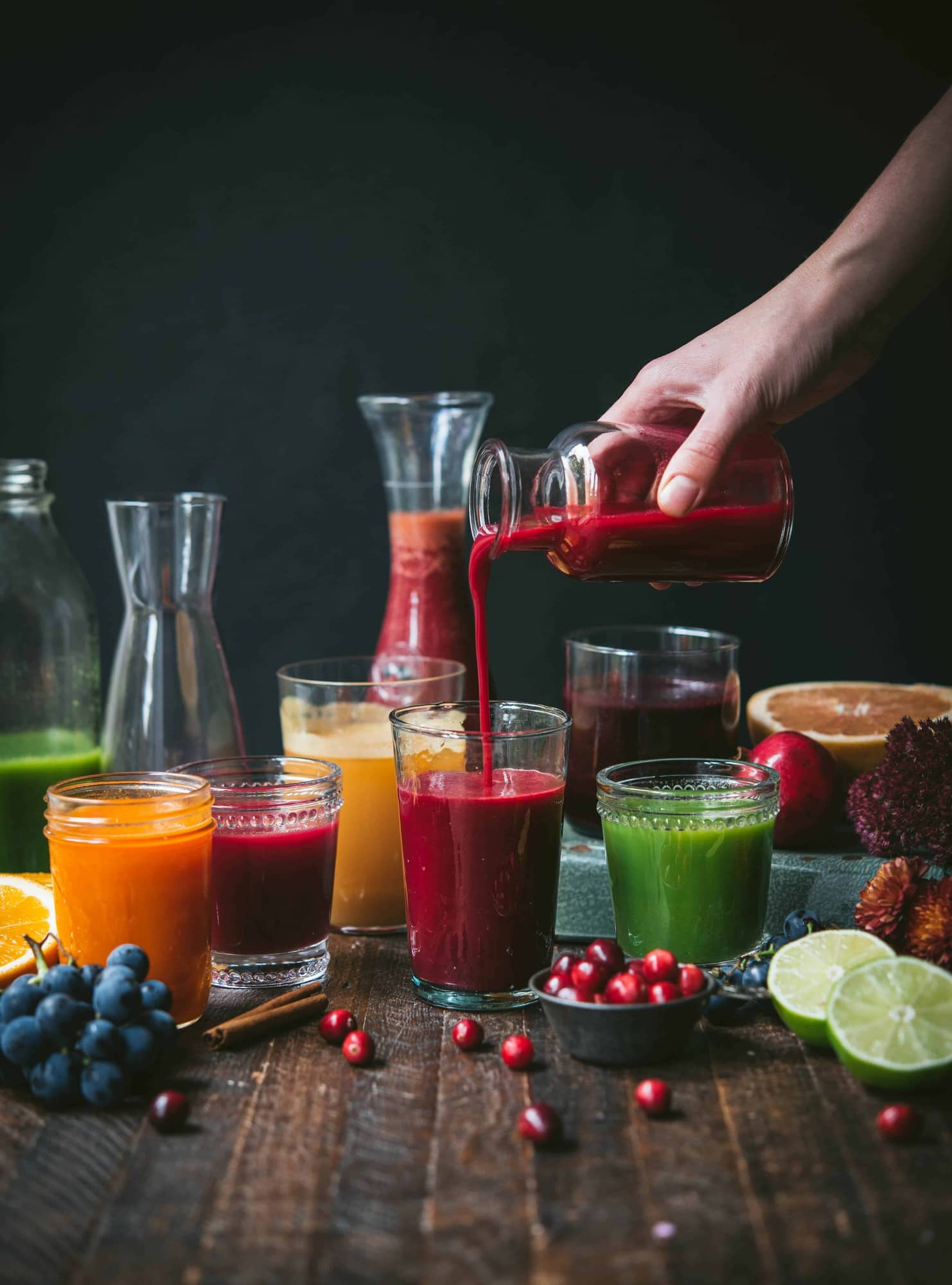 Side view of glasses and carafes of fresh fall juices, hand pouring juice into glass