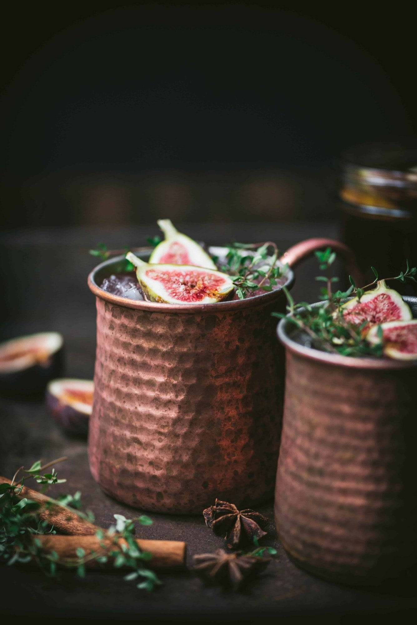 Side view of fig moscow mule vodka cocktail in copper mug with cinnamon sticks and fresh thyme