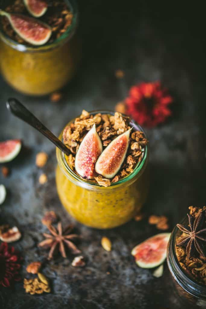 High side view of pumpkin chia pudding in a small glass jar topped with fresh figs and granola. Styled on a dark, rustic background