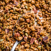 close up view of pumpkin spice granola on a large serving spoon on sheet pan.