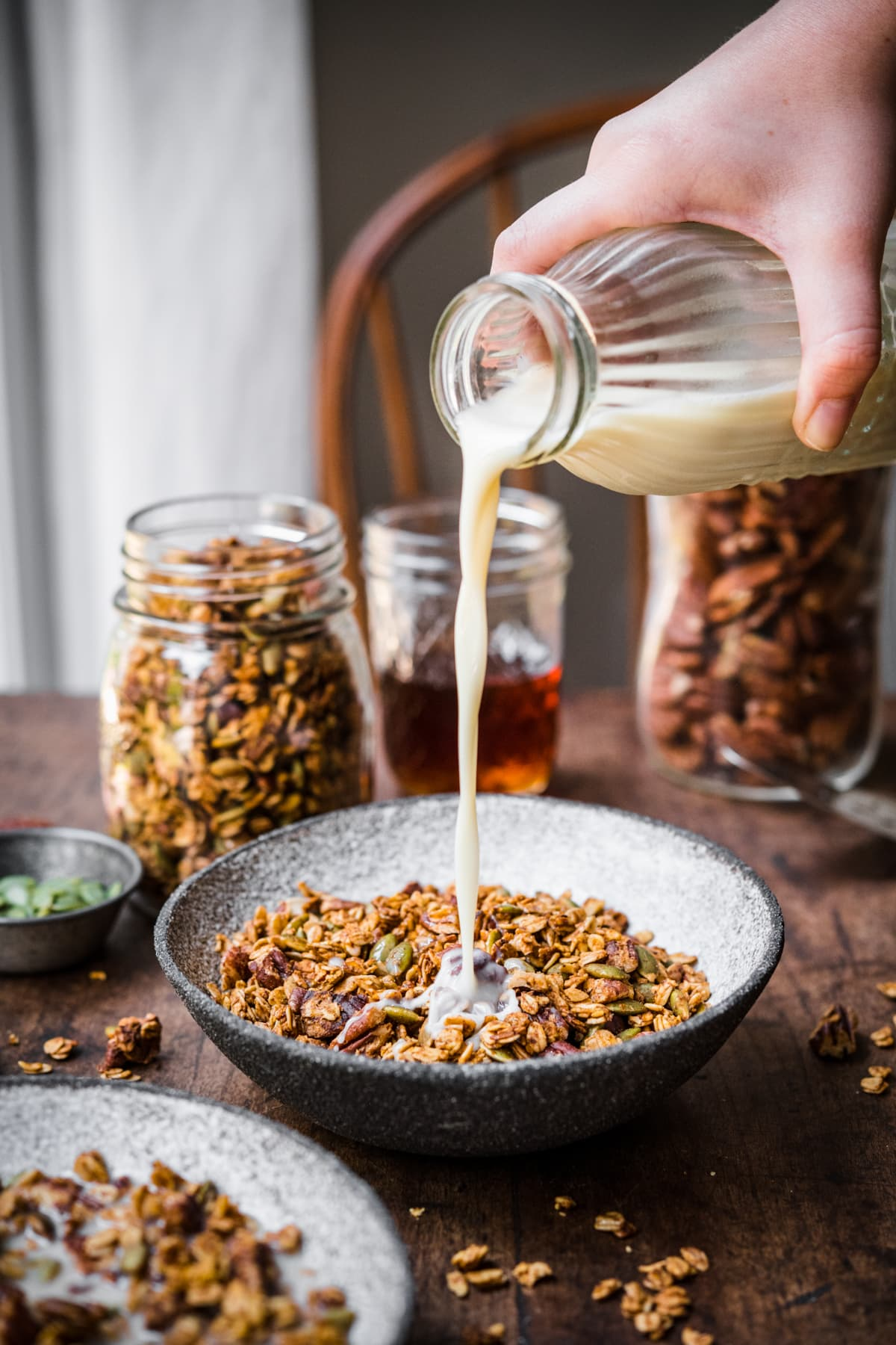 Pouring milk into a bowl of pumpkin spice granola on wood table.