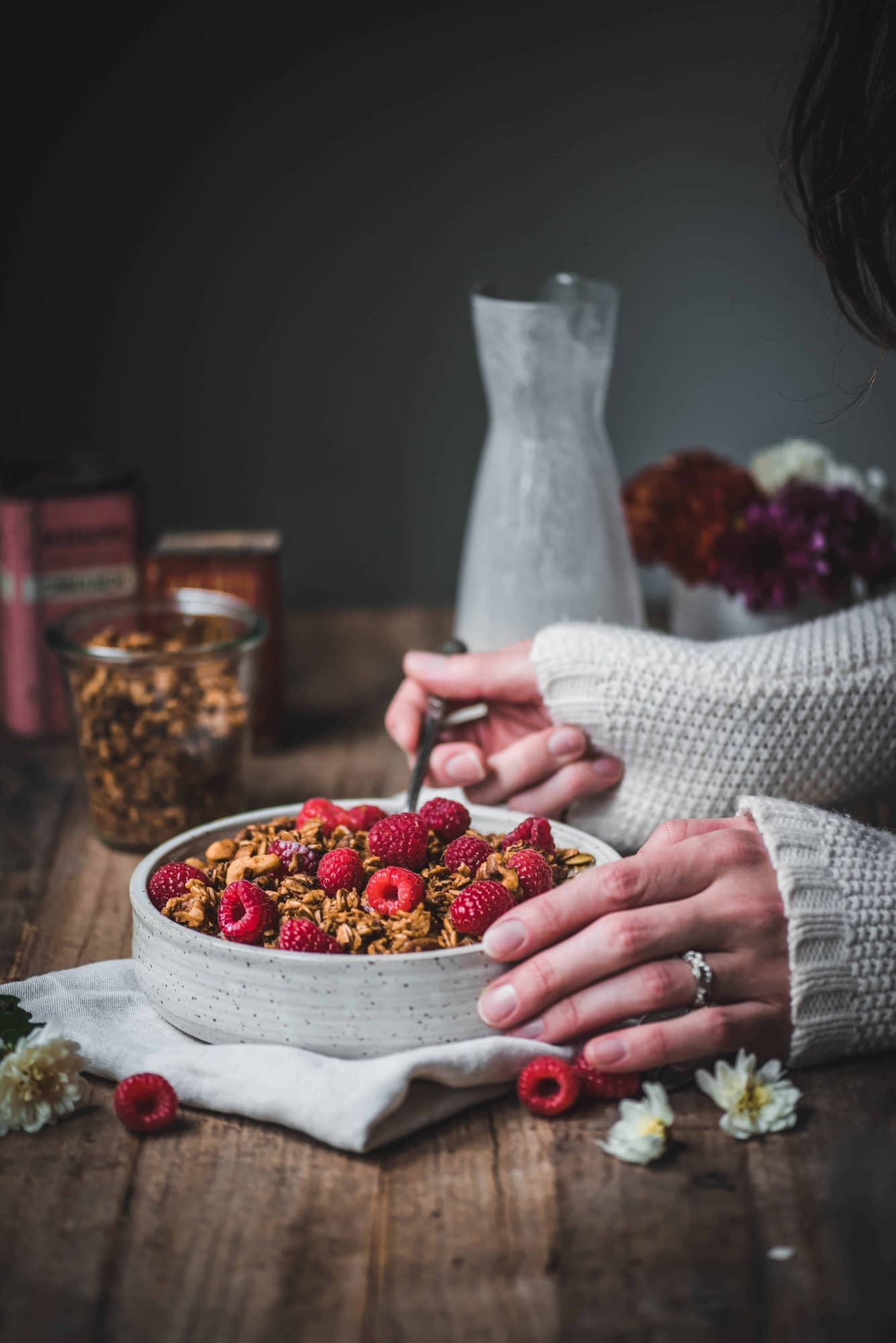 Side view of pumpkin spice granola with milk and fresh raspberries in a white bowl on rustic wood table. Person holding spoon about to eat granola