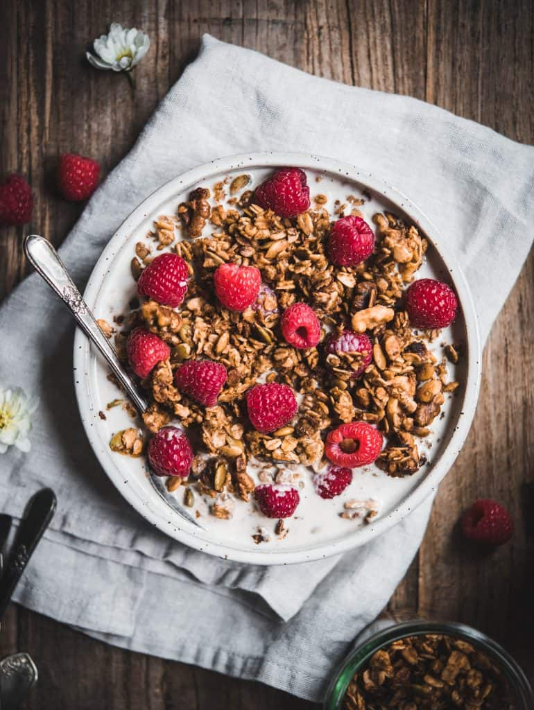 Overhead of granola with milk and fresh raspberries in a white bowl