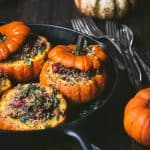 Side view of Stuffed Mini Pumpkins with Wild Rice and Mushrooms in a cast iron skillet
