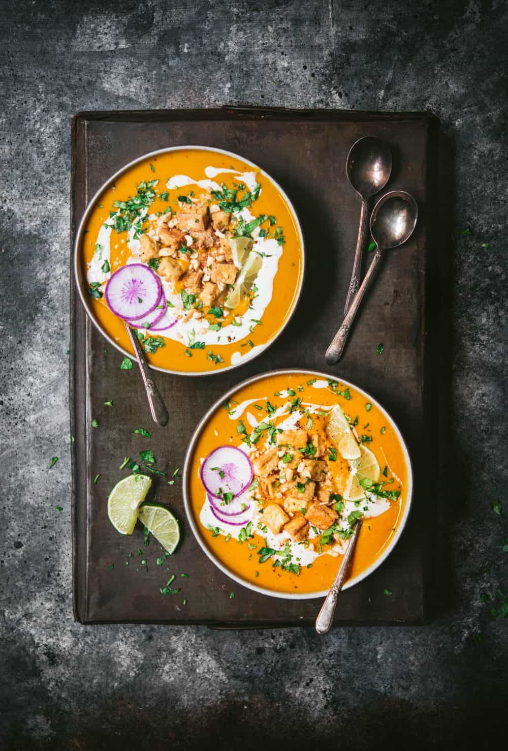 Overhead of two bowls of thai red curry pumpkin soup in black bowl garnished with crispy tofu, lime, fresh herbs and purple daikon radish