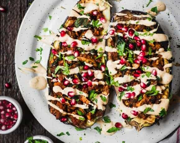 Stuffed roasted eggplants drizzled with tahini and pomegranate on a white plate