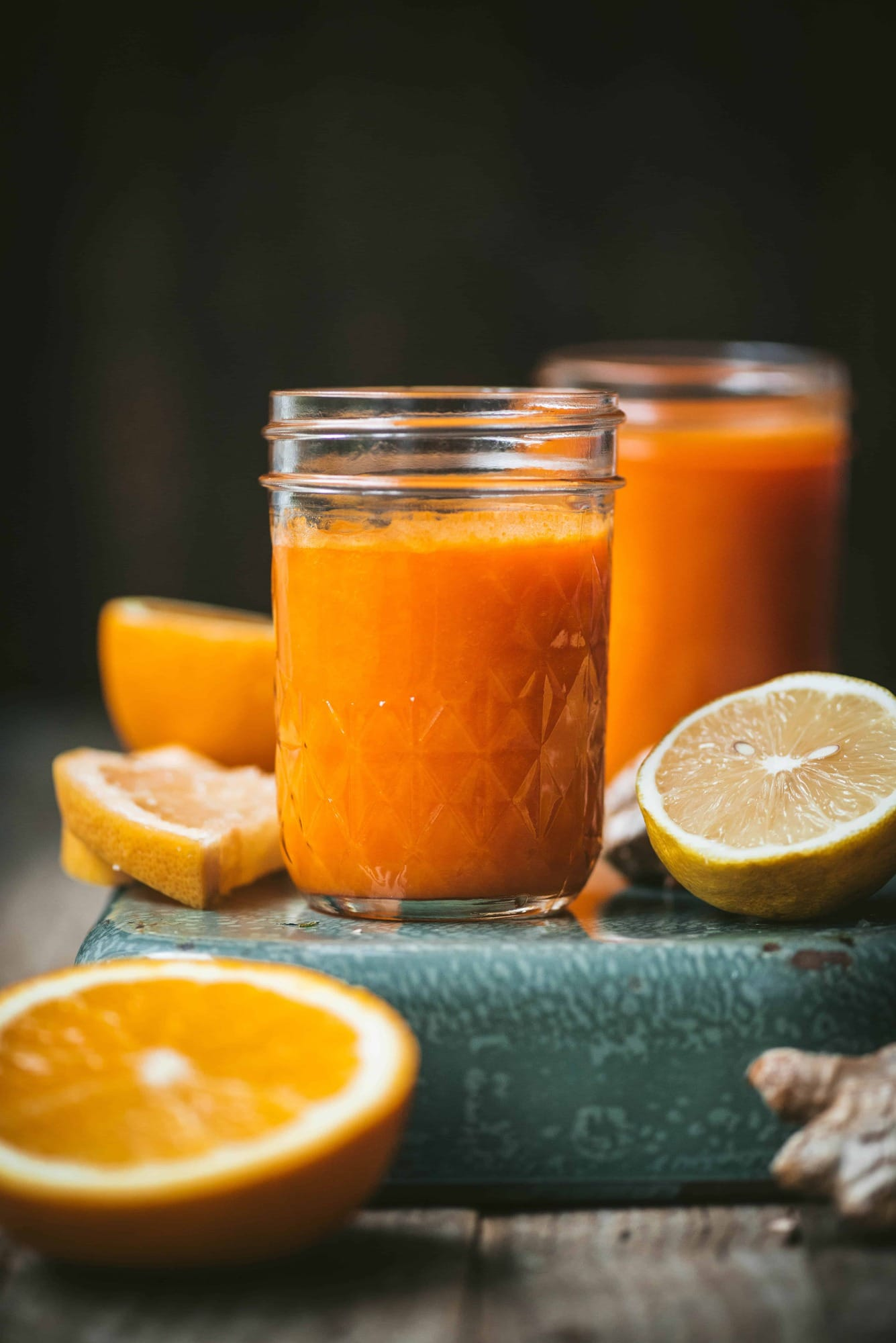 Close up of homemade orange juice with fresh lemons and oranges on a teal background