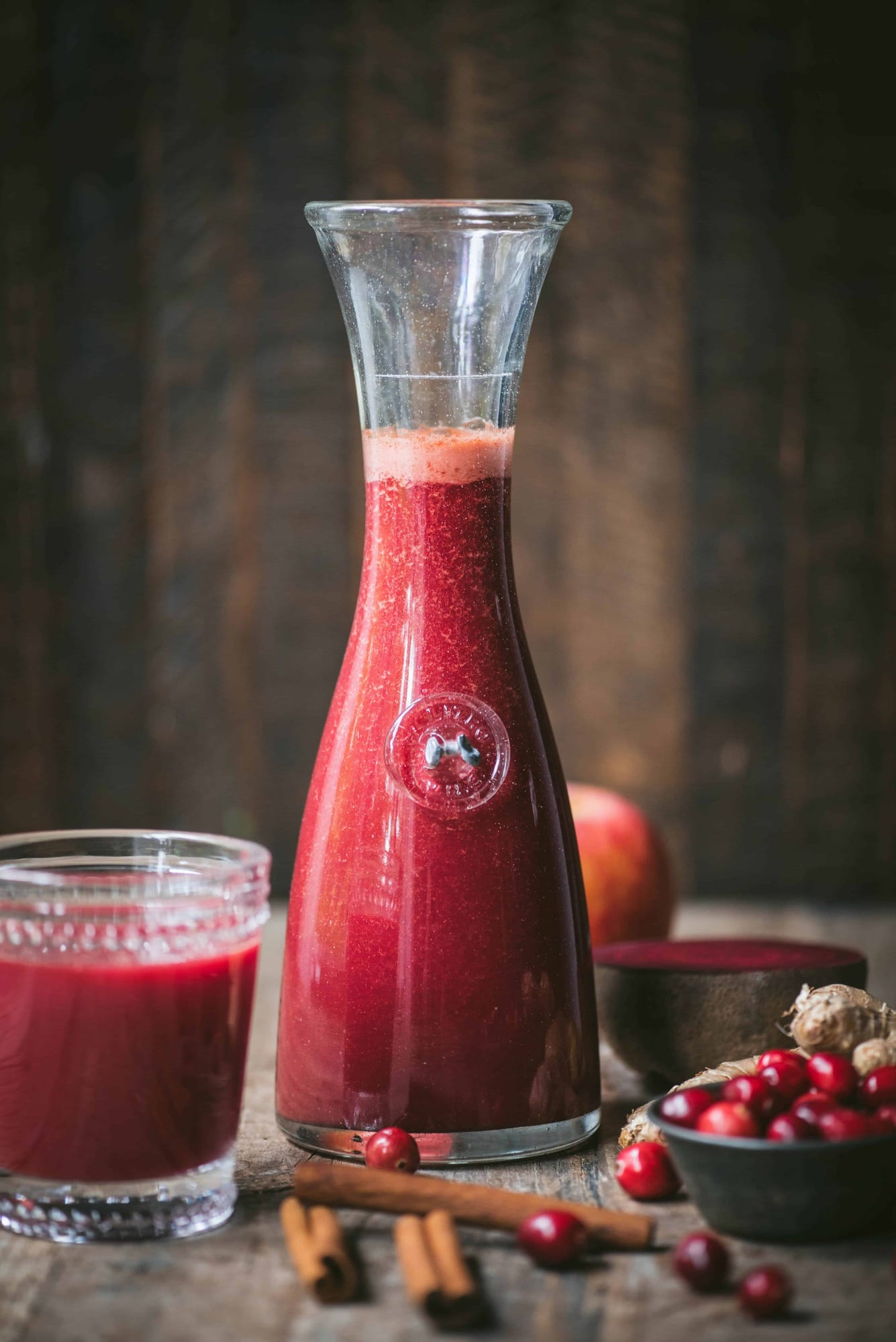 Red juice in a tall carafe on rustic wood background