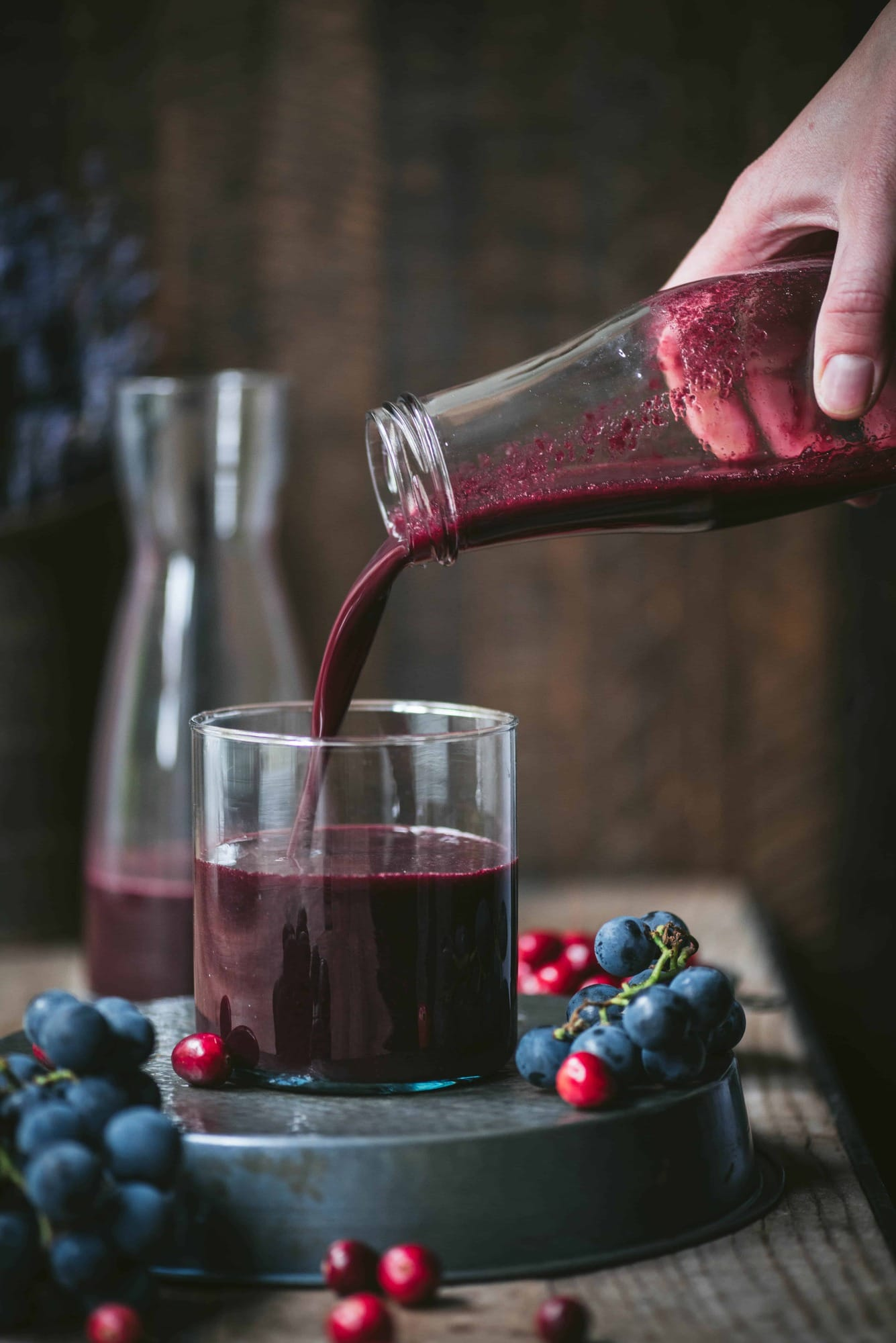Homemade concord grape and cranberry juice being poured into a glass