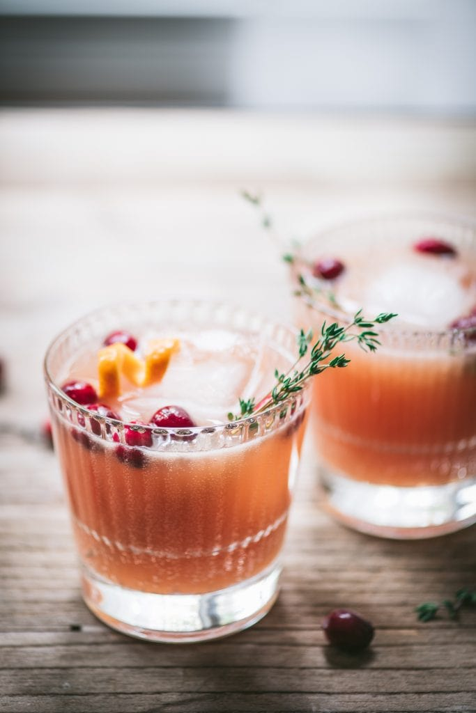 Two cranberry orange cocktails garnished with fresh thyme on a wood table with window in background