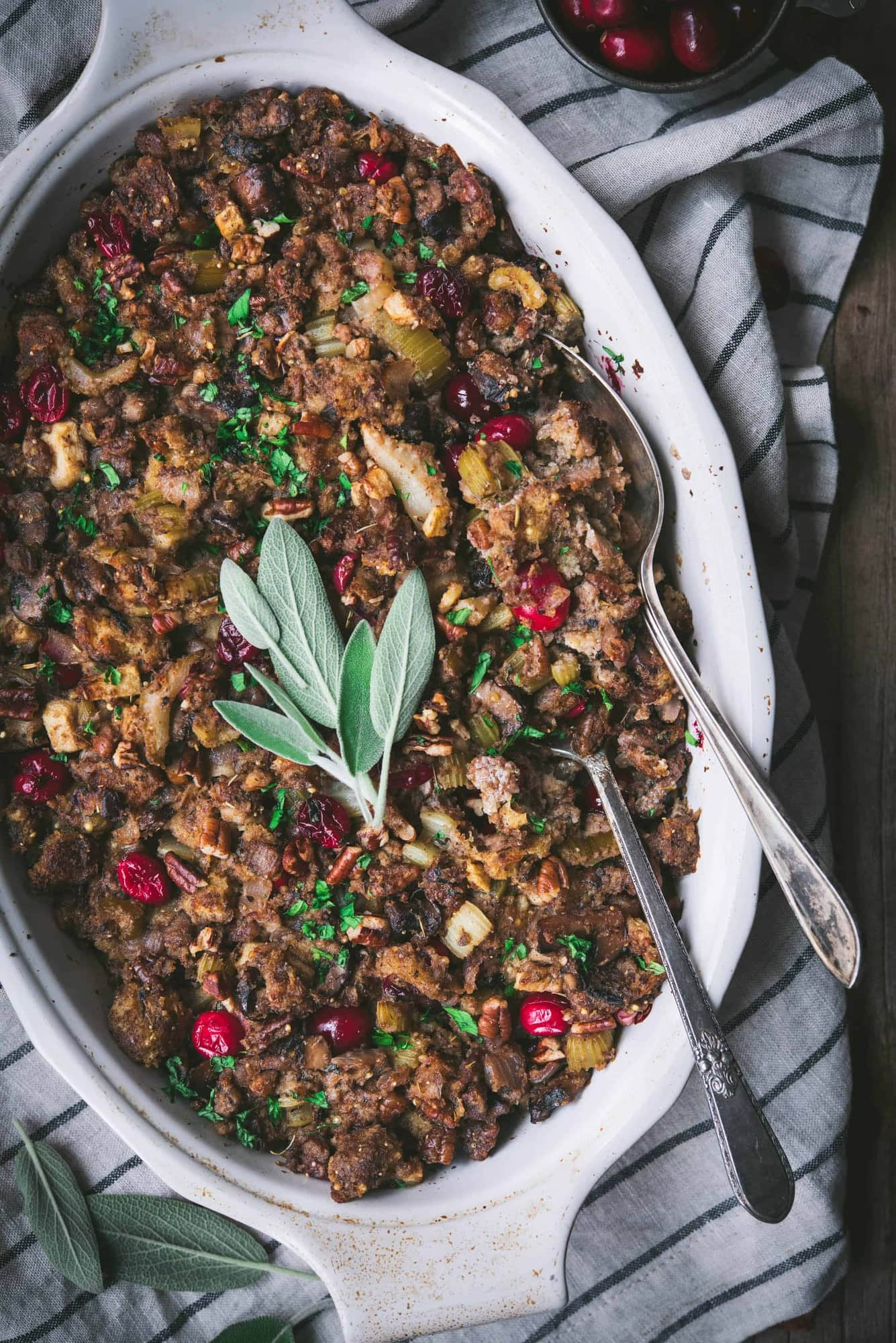 Close up of gluten free stuffing with fresh sage in an oval baking pan with two spoons